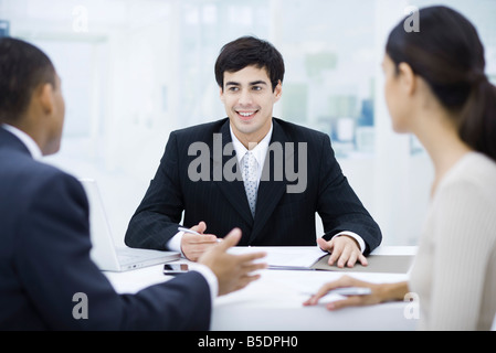 Businessman sitting at desk, talking with clients and smiling - Stock Photo
