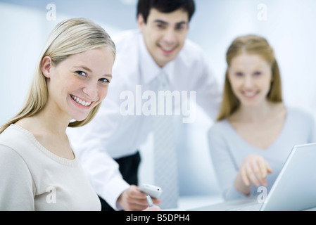 Young female professional smiling at camera, colleagues in background - Stock Photo