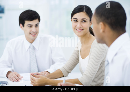 Young professionals sitting at table, focus on woman in center - Stock Photo