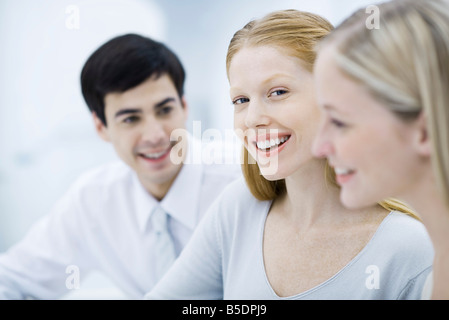 Young professional woman between two colleagues, smiling at camera - Stock Photo