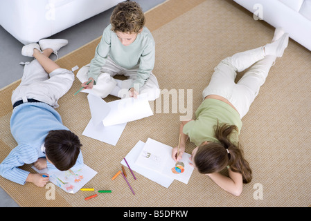Three children coloring on the floor, high angle view - Stock Photo