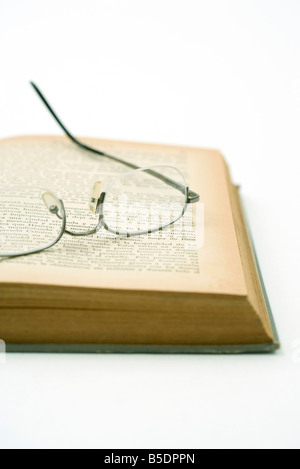 Pair of glasses resting on yellowed page of open book - Stock Photo