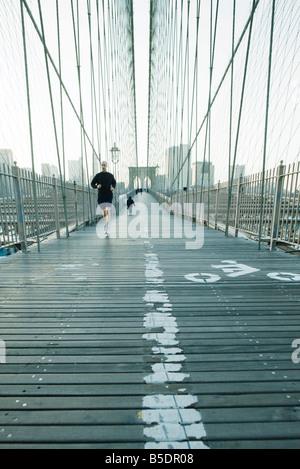 Jogger running across pedestrian walkway of Brooklyn Bridge in New York City, Manhattan skyline in distance - Stock Photo