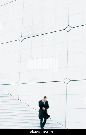 Businessman descending outdoor stairs, talking on cell phone, holding coat closed against the wind - Stock Photo