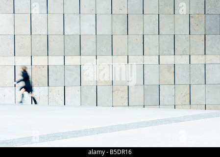Woman hurrying from top of stairs down sidewalk - Stock Photo