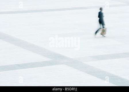 Woman walking across public square - Stock Photo