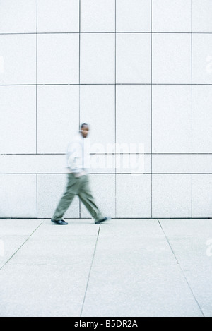 Man walking with hands in his pockets down sidewalk - Stock Photo
