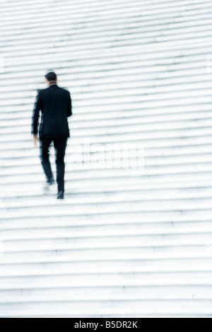 Businessman ascending stairs outdoors - Stock Photo