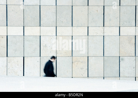 Businessman descending stairs leading down from sidewalk - Stock Photo