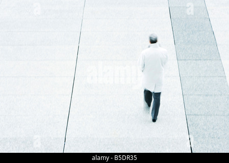 High angle rear view of business man walking down sidewalk - Stock Photo