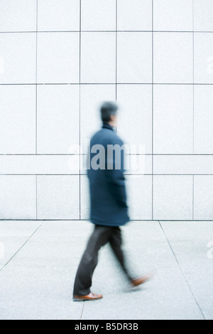 Man walking with hands in pockets down sidewalk - Stock Photo