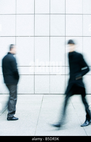 Two men passing one another as they walk along the sidewalk - Stock Photo