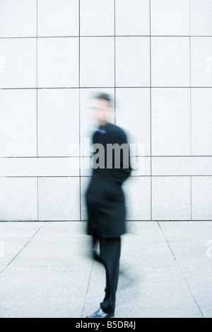 Businessman hurrying down sidewalk - Stock Photo