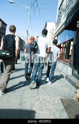 Young men walking NE along sidewalk on 8th Avenue in Chelsea, New York City, rear view - Stock Photo