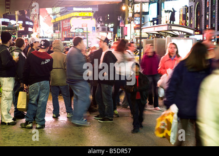 Crowd scene on sidewalk near bus stop on Broadway in New York City looking north at Times Square - Stock Photo