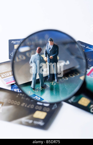 Miniature businessmen shaking hands on pile of credit cards, viewed through magnifying glass - Stock Photo