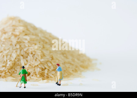Miniature women sweeping up giant pile of rice - Stock Photo