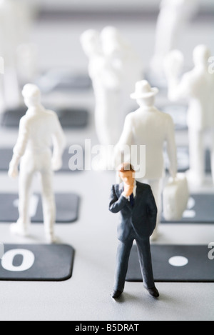 Miniature man figure in suit standing with hand under chin, white figures in the background - Stock Photo