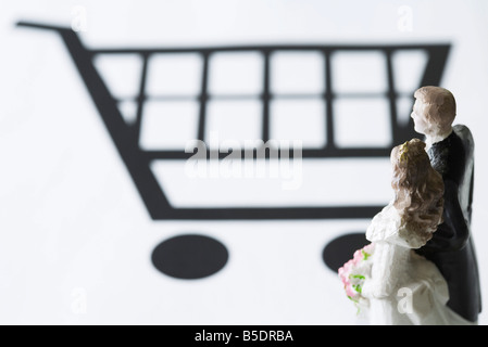 Bride and groom figures looking at shopping cart - Stock Photo