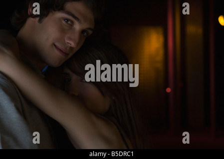 Couple embracing in darkly lit room, looking over shoulder at camera - Stock Photo