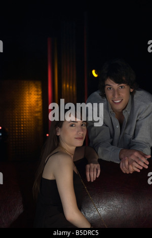 Couple in nightclub, smiling at camera, portrait - Stock Photo