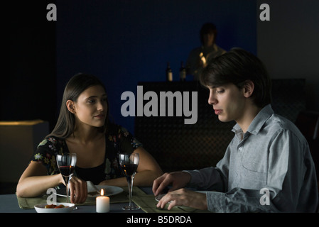 Couple having serious conversation over dinner with wine at restaurant - Stock Photo