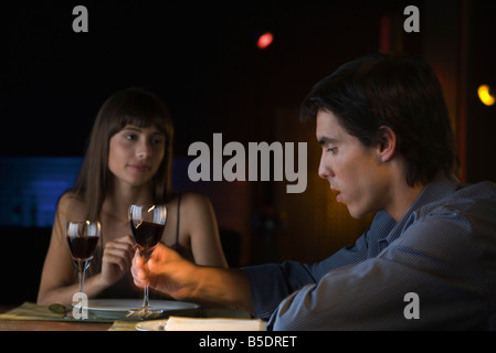 Couple having serious conversation over dinner at restaurant, man picking up glass of wine - Stock Photo