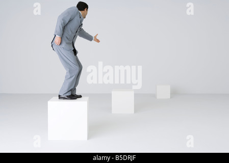 Businessman standing on block, reaching out hand - Stock Photo