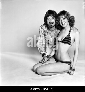 Couple wearing 1970s fashion. The woman wearing a matched striped bikini with the man wearing a floral patterned - Stock Photo