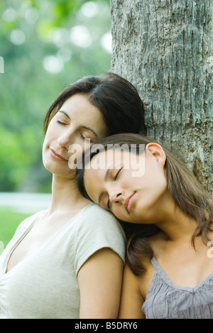 Mother and teen daughter leaning against tree with eyes closed, daughter's head on mother's shoulder - Stock Photo