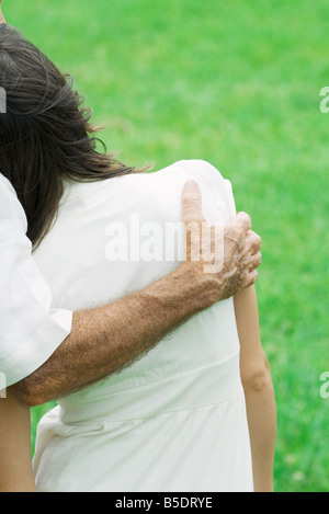 Young female leaning head on man's shoulder, cropped rear view - Stock Photo