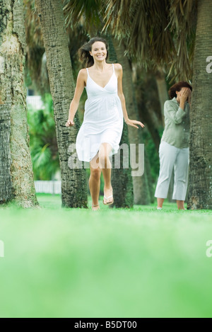 Mother and teen daughter playing hide-and-seek in park, girl running toward camera - Stock Photo