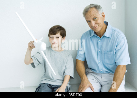 Grandfather sitting with grandson, smiling as grandson plays with toy airplane - Stock Photo
