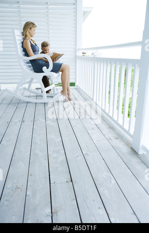 Woman sitting in rocking chair on porch, reading story to little boy standing at her side - Stock Photo