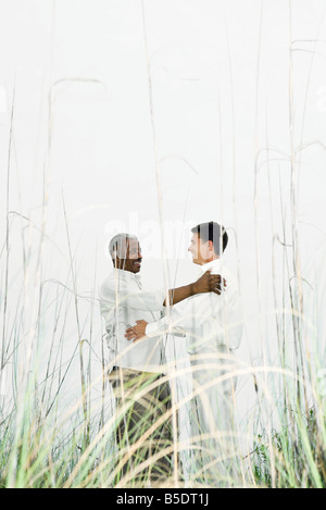 Two men facing each other in tall grass, smiling, embracing - Stock Photo