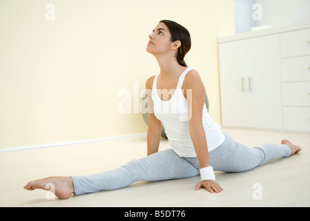 Young woman doing splits, looking up - Stock Photo