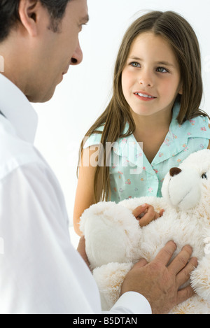 Pediatrician with young patient, girl holding teddy bear - Stock Photo