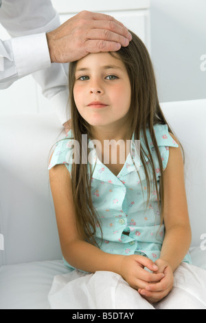 Doctor placing his hand on little girl's forehead, cropped view - Stock Photo