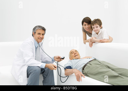 Doctor measuring elderly man's blood pressure, family leaning on couch, all smiling at camera - Stock Photo