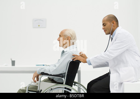 Elderly man sitting in wheelchair, doctor using stethoscope on back - Stock Photo