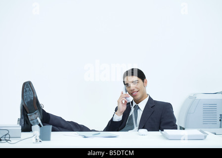 Young businessman sitting at desk with feet up, talking on landline phone - Stock Photo
