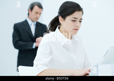 Young woman typing on laptop, boss checking time in background - Stock Photo