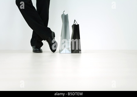 Man standing next to shopping bags, cropped view of feet, low angle view - Stock Photo