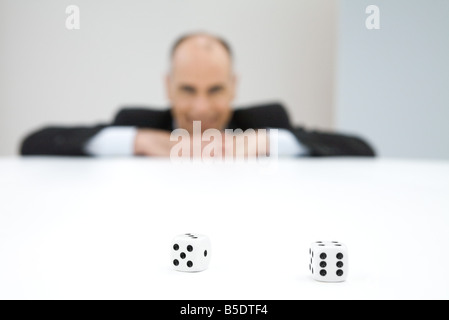 Pair of dice, businessman in background - Stock Photo