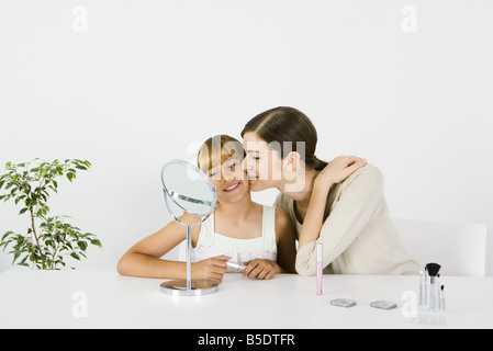 Young woman and preteen sister sitting in front of mirror, older sister kissing younger sister's cheek - Stock Photo