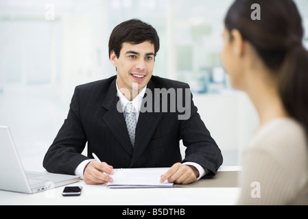 Businessman sitting at desk, talking with woman and smiling - Stock Photo