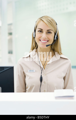 Professional woman wearing headset, smiling at camera - Stock Photo
