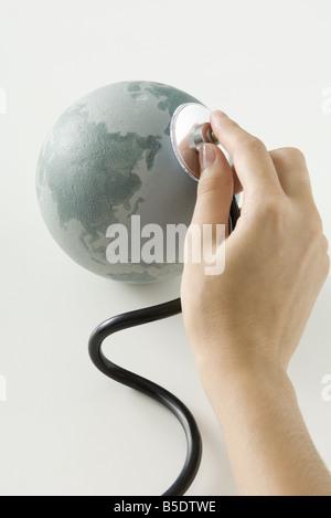 Hand holding stethoscope on small globe - Stock Photo