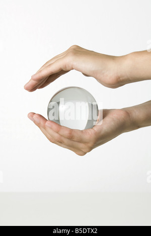 Hands holding crystal ball - Stock Photo