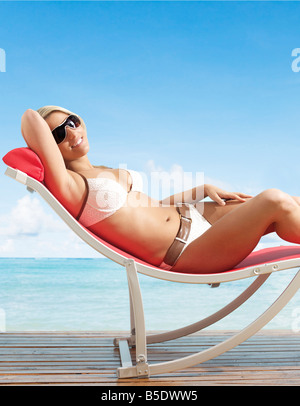 Young Woman Relaxing on Lounge Chair - Stock Photo